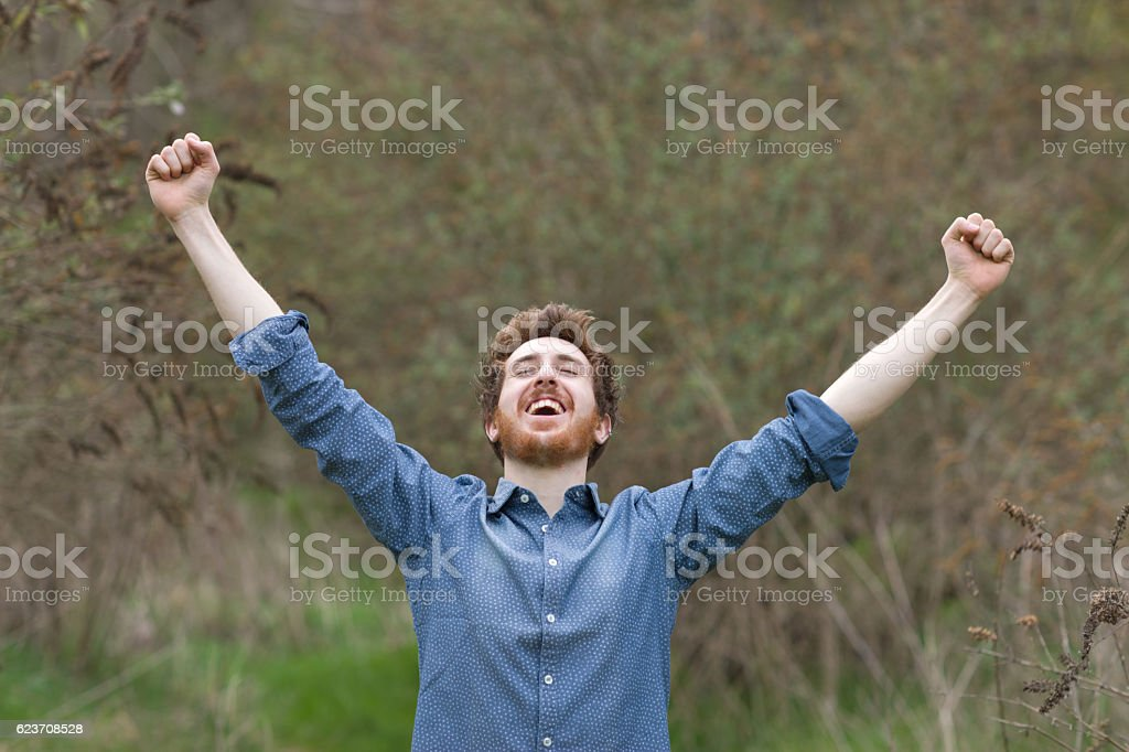 Cheerful hipster with raised fists stock photo