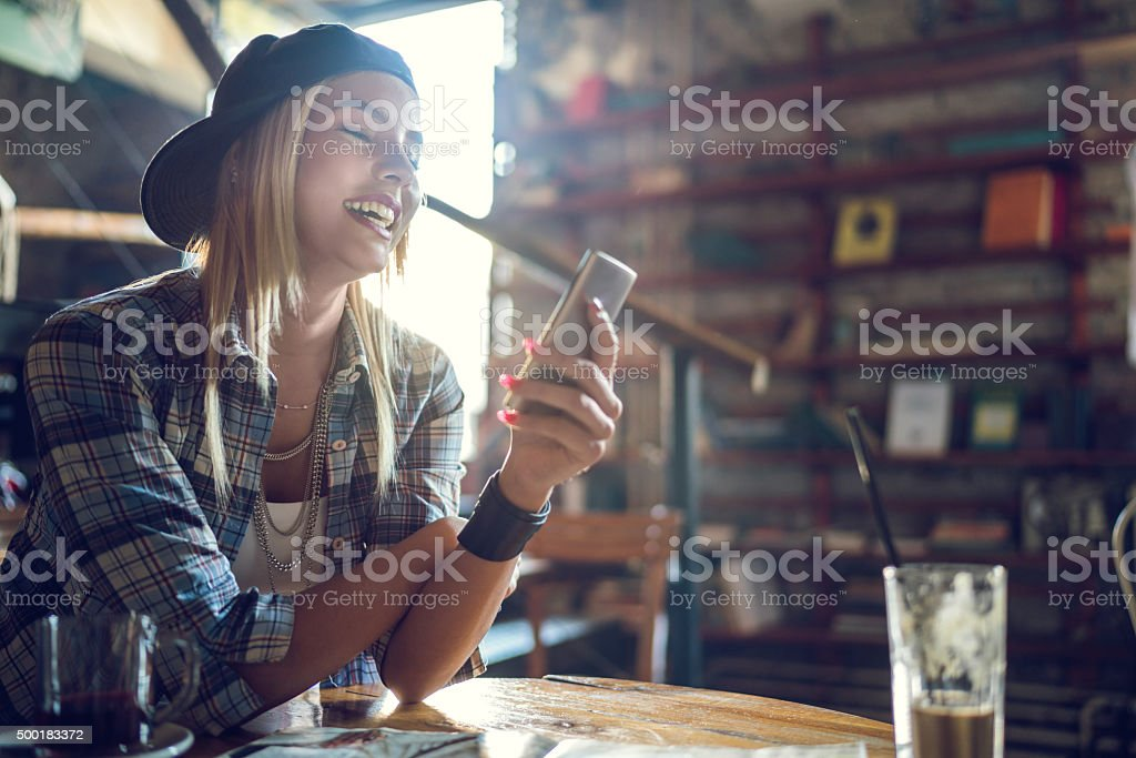 Cheerful hipster woman using mobile phone in a cafe. stock photo