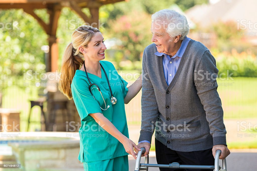 Cheerful home healthcare nurse takes care of senior patient stock photo