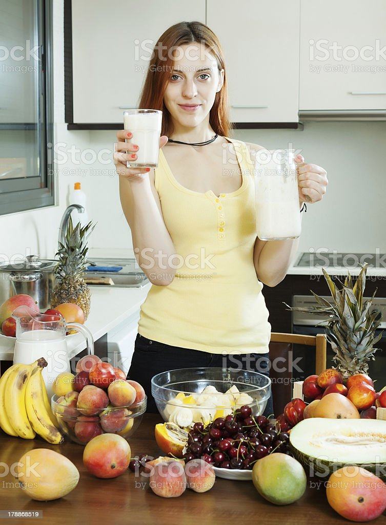 cheerful housewife drinking milk cocktail with fruits royalty-free stock photo