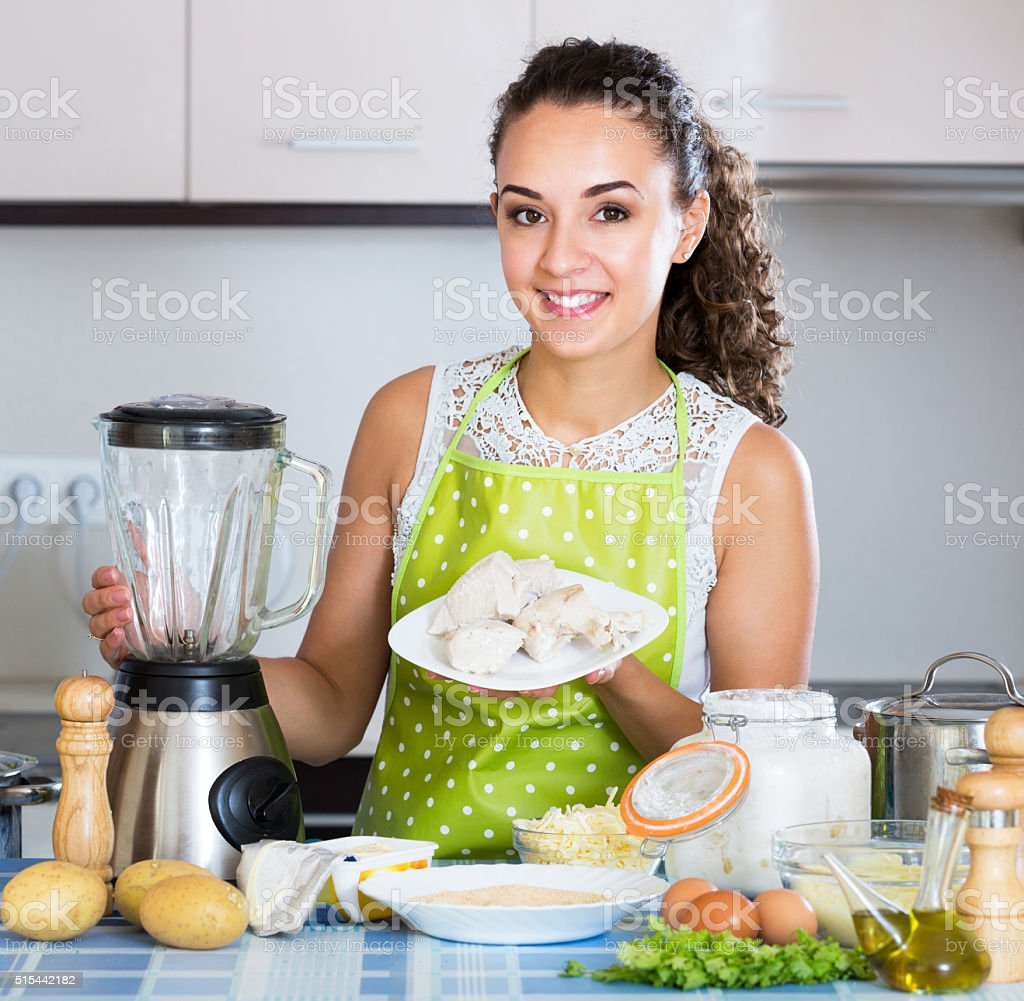 Cheerful housewife grinding paste ingredients stock photo
