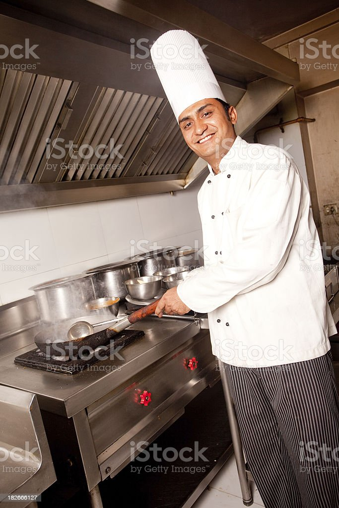 Cheerful Indian Chef working cooking in a Restaurant Kitchen Vertical royalty-free stock photo