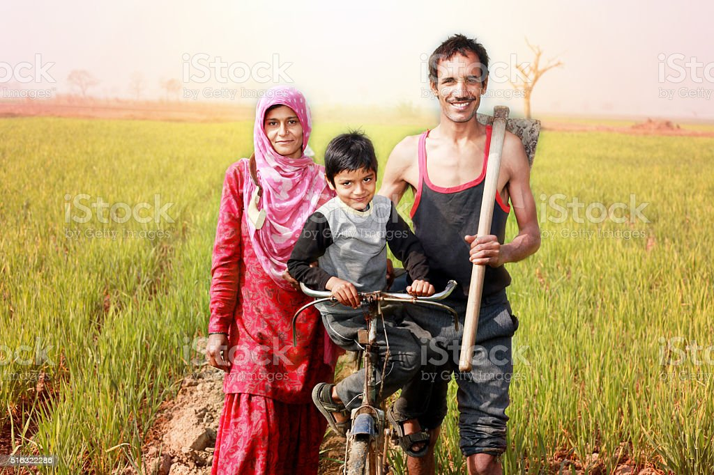 Cheerful Indian family standing in the field with bicycle stock photo