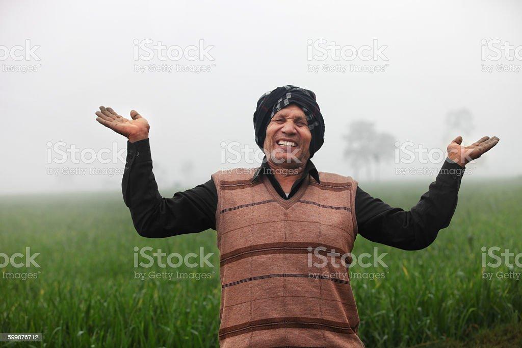 Cheerful Indian farmer in wheat field stock photo