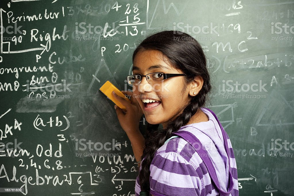 Cheerful Indian Girl Student Erasing Mathematics Problems from Greenboard Blackboard royalty-free stock photo