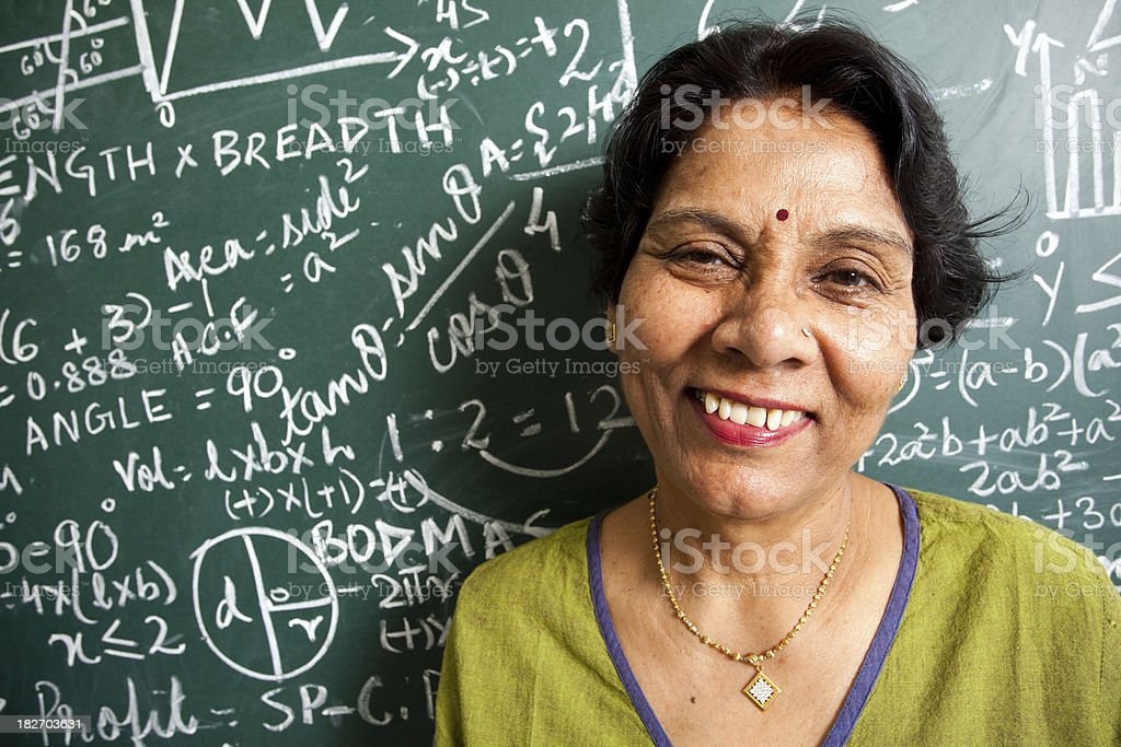 Cheerful Indian math teacher with blackboard royalty-free stock photo
