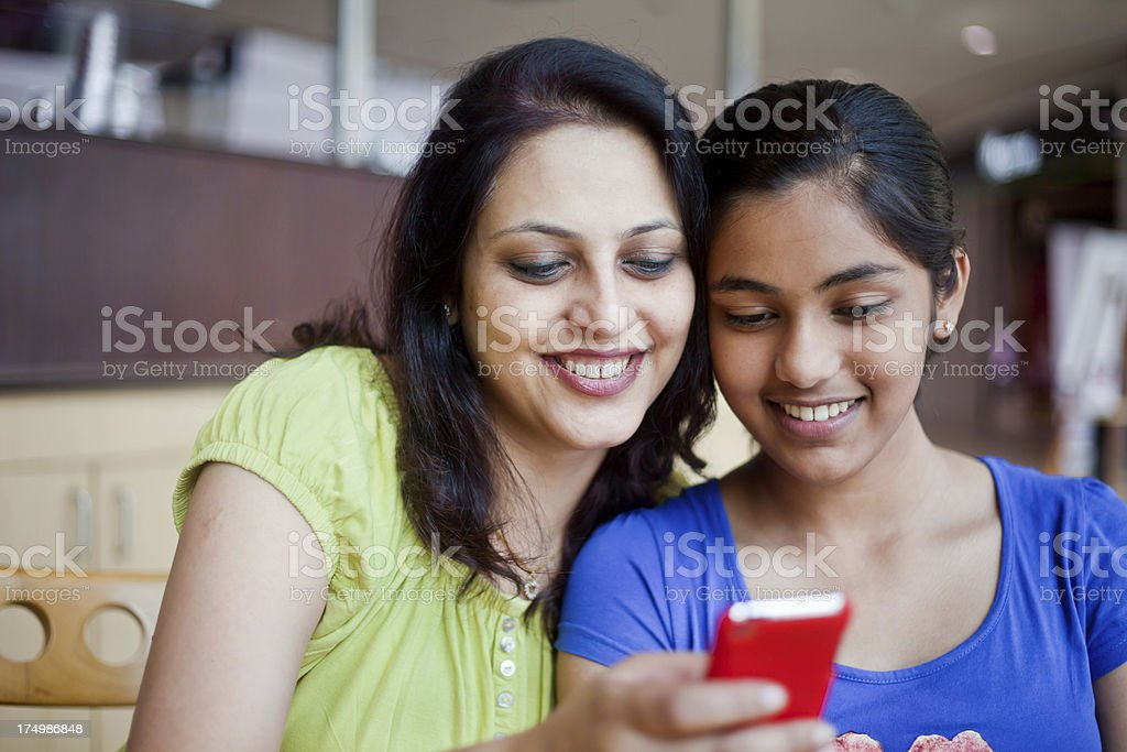 Cheerful Indian Mother and Daughter Sending Reading SMS at Cafeteria royalty-free stock photo