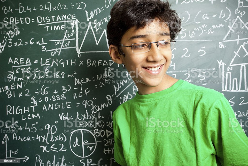 Cheerful Indian Teenager Boy Student with Mathematics Problems stock photo