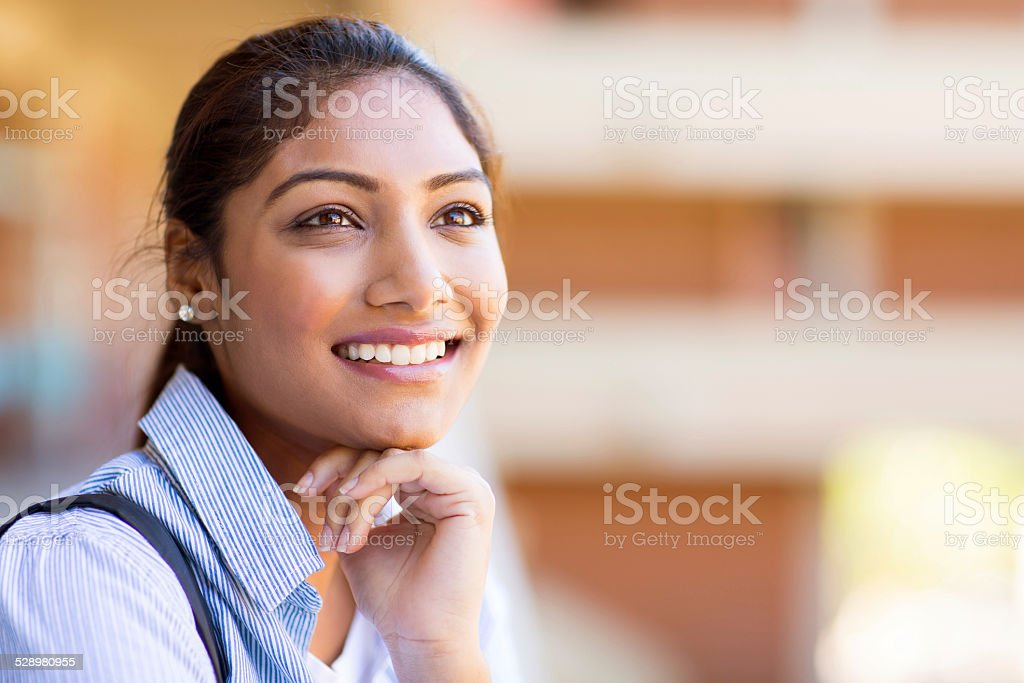 cheerful indian university girl daydreaming stock photo
