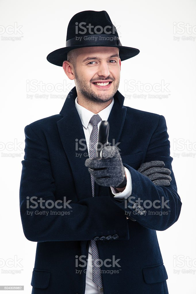 Cheerful investigator in coat, hat and gloves pointing on you stock photo