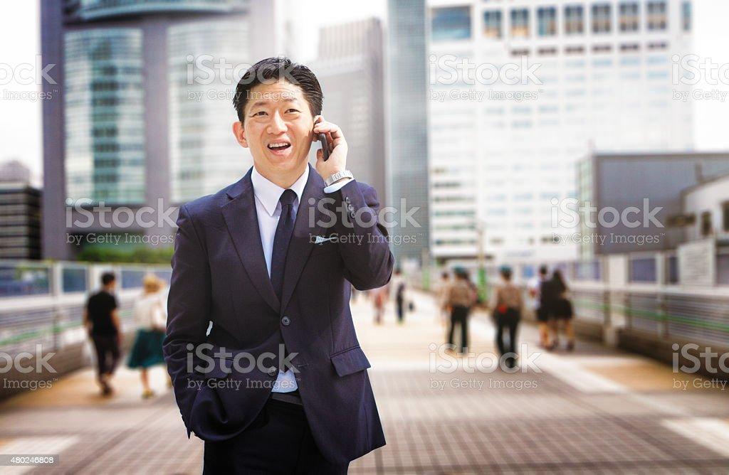 Cheerful Japanese businessman on the phone walking in Shinjuku...