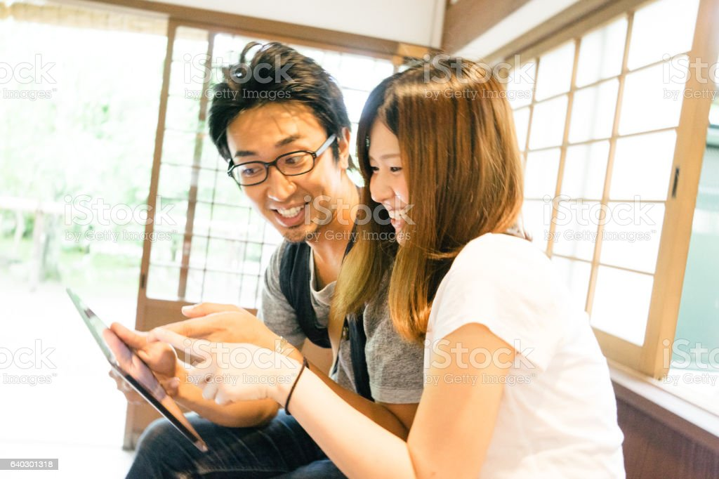 Cheerful Japanese friends using tablet indoors stock photo