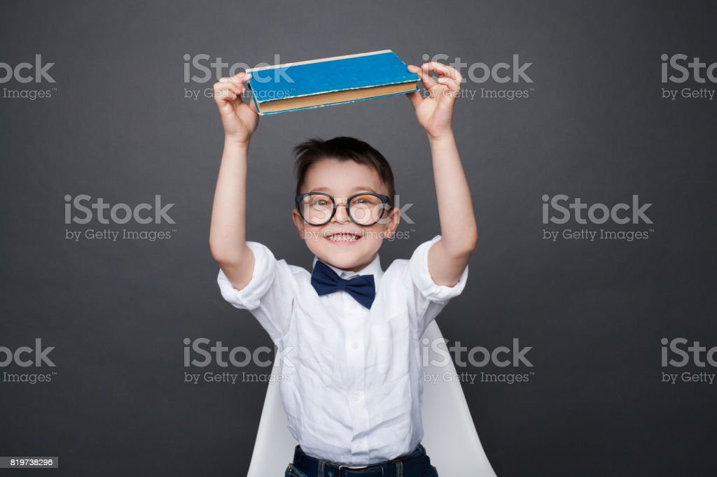 Smart boy in glasses sitting on chair and holding book above head...