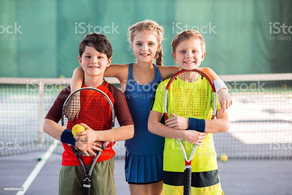 We like tennis. Happy girl is embracing two boys while standing on...