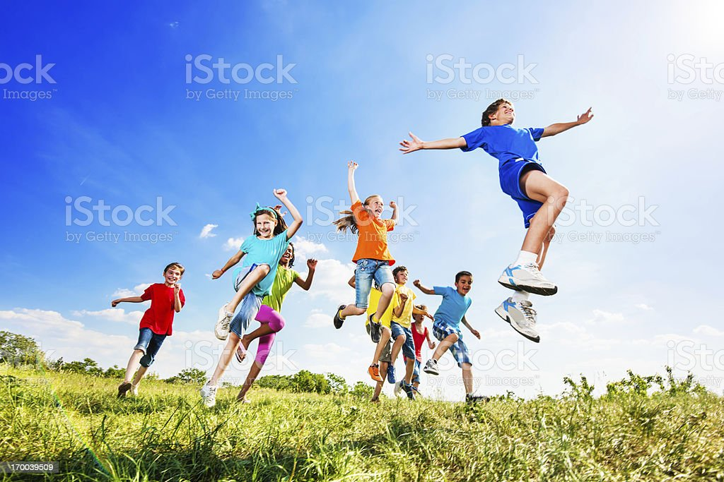 Cheerful kids jumping in field against the sky. stock photo