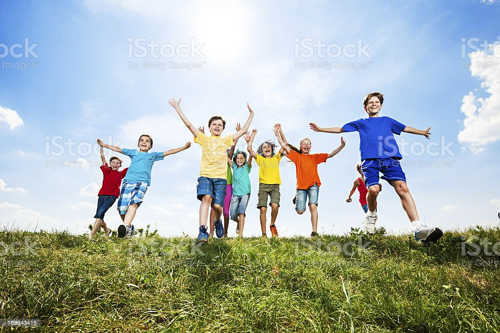 Cheerful kids running in the field. royalty-free stock photo