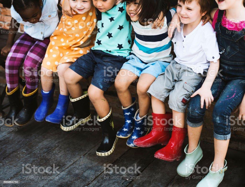 Cheerful kindergarten kids friends arm around sitting stock photo