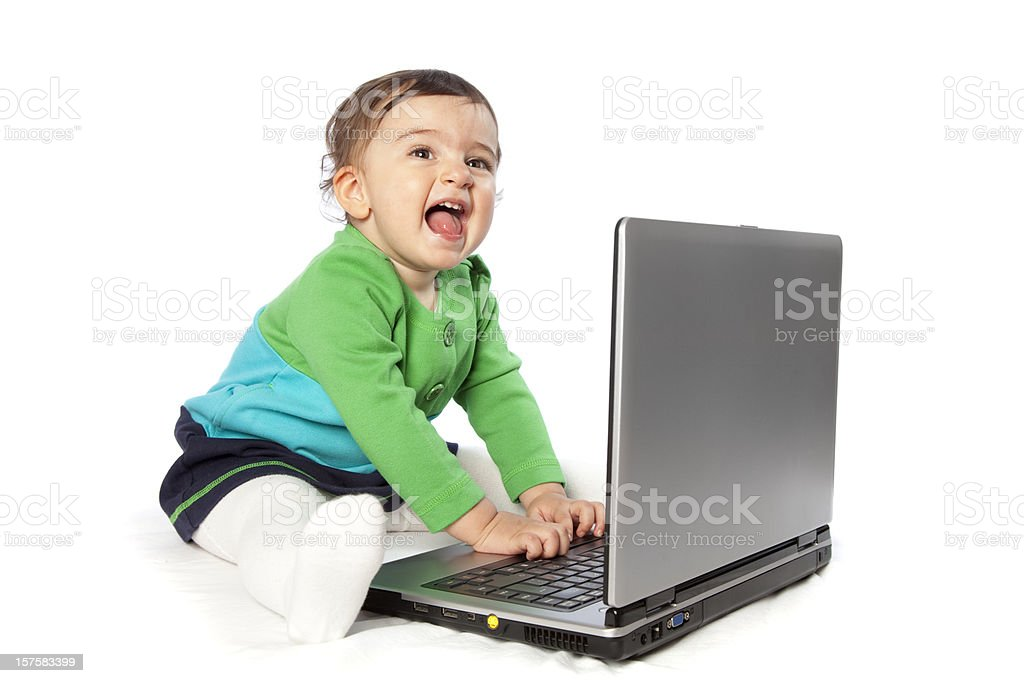 Cheerful little baby girl with laptop laughing stock photo
