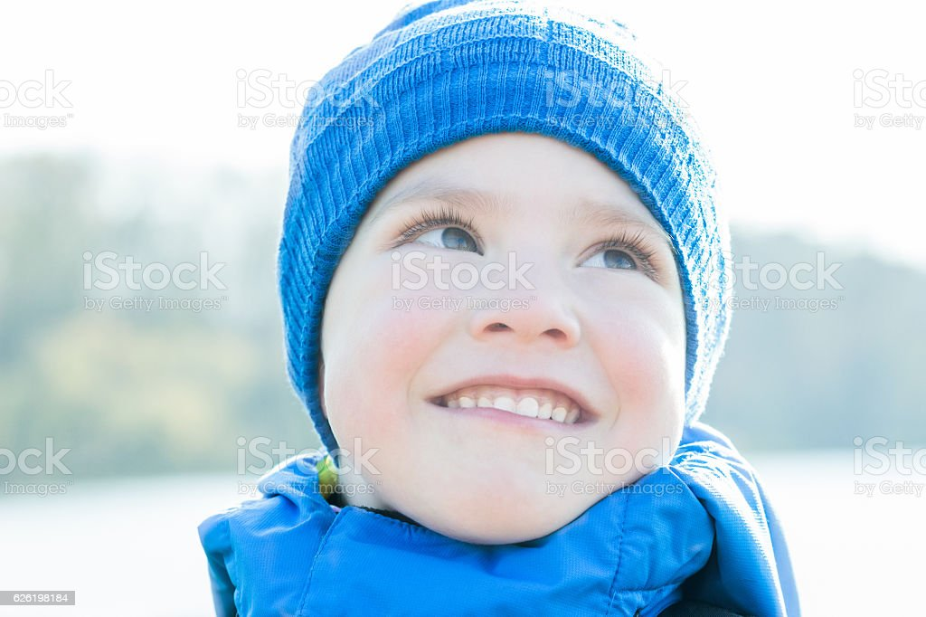 Cheerful little boy close-up portrait with blue knitted hat stock photo