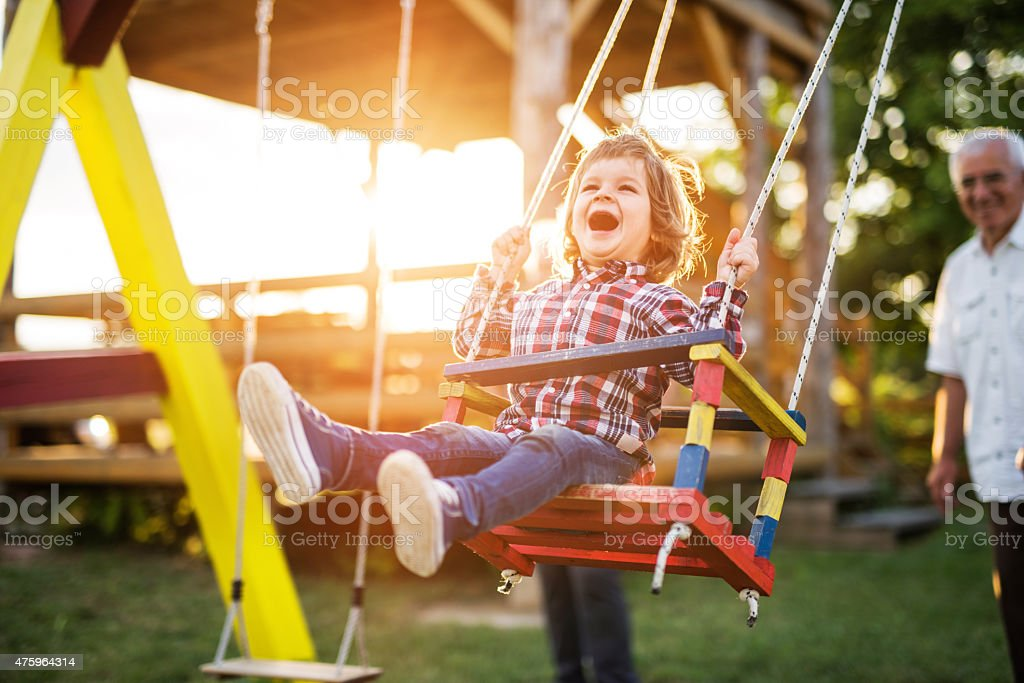 Cheerful little boy enjoying on a swing at sunset. stock photo