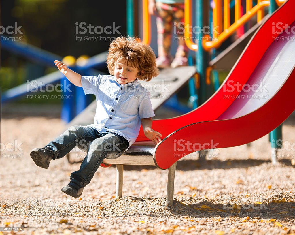 Cheerful little boy having fun while sliding outdoors. stock photo