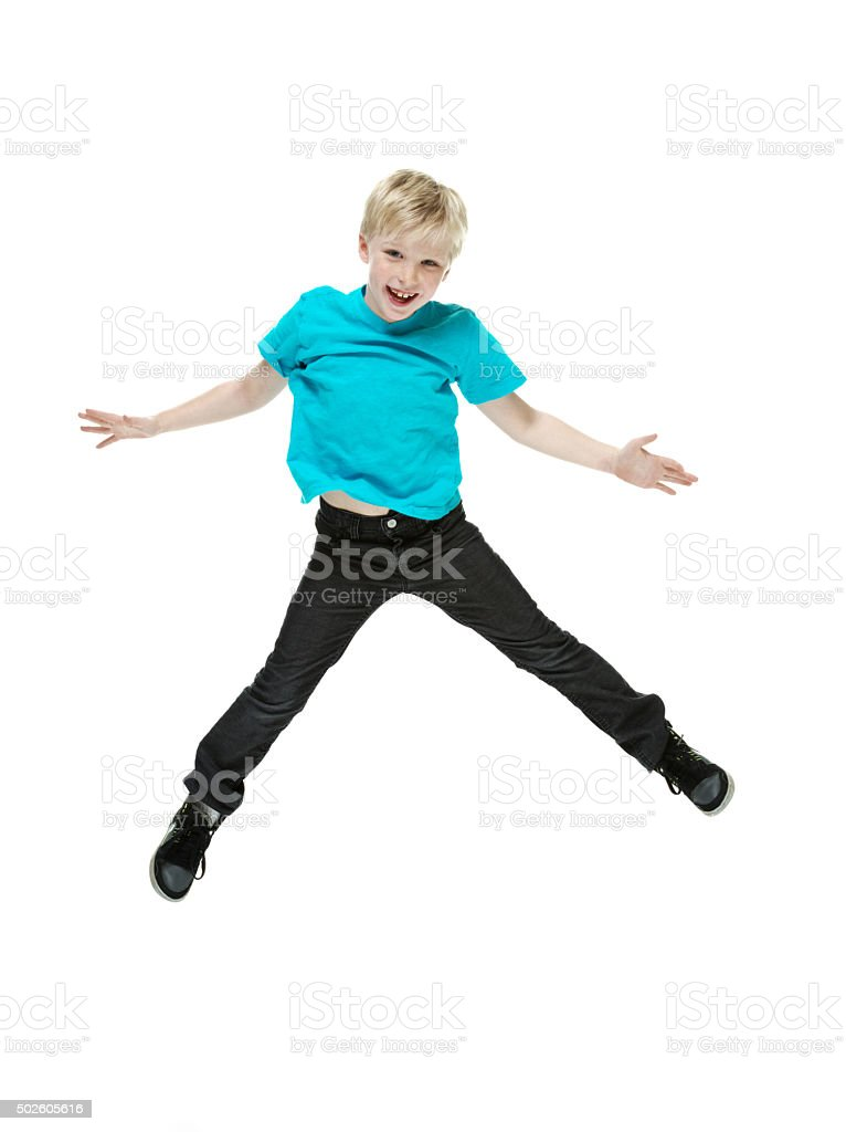 Cheerful little boy jumping and cheering stock photo