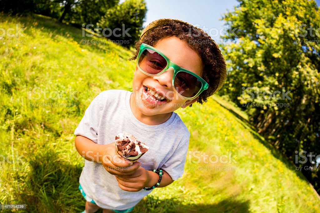 Cheerful little boy licking ice cream on a sunny day stock photo