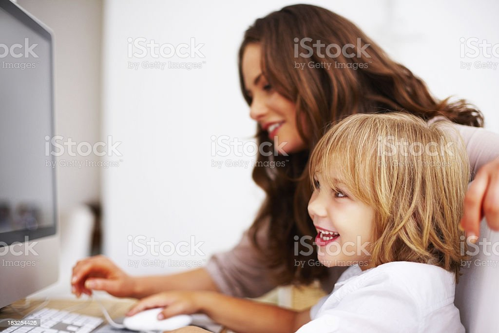 Cheerful little boy with his mother working on computer royalty-free stock photo