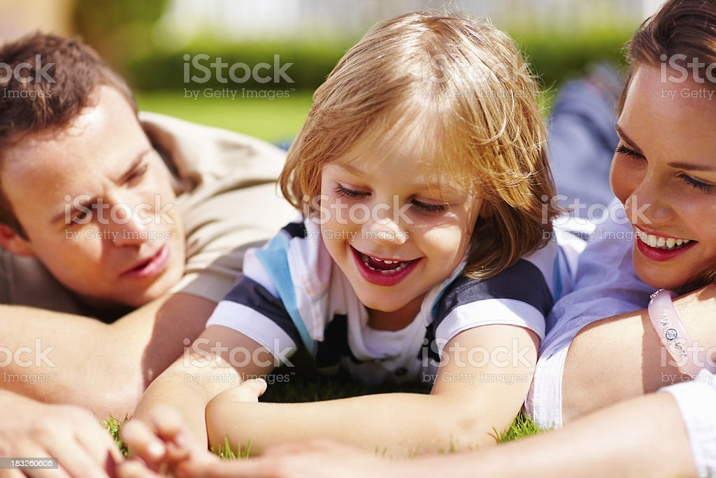 Cheerful little boy with his parents lying on green grass royalty-free stock photo