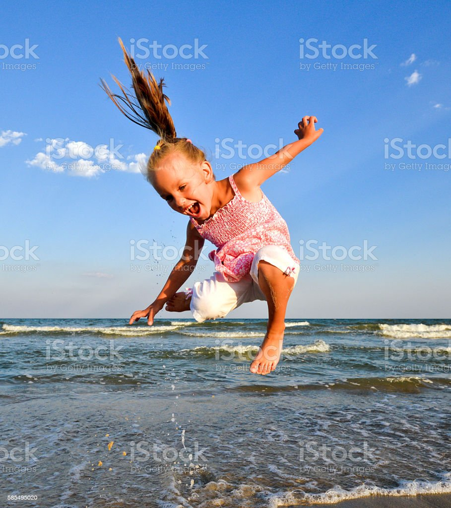 Cheerful little child girl jumping and hovering in the air stock photo