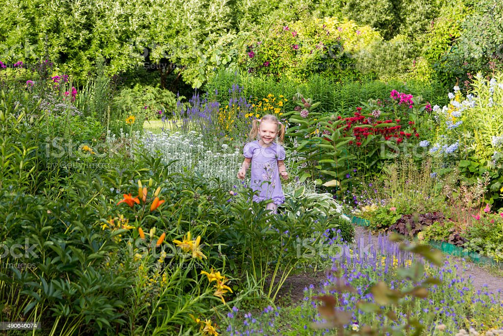 cheerful little girl among flowers in park stock photo