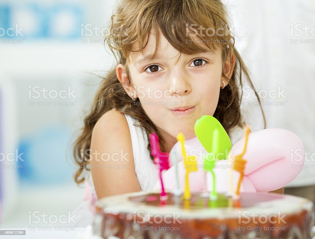 Cheerful Little Girl Blowing Birthday Candles. royalty-free stock photo