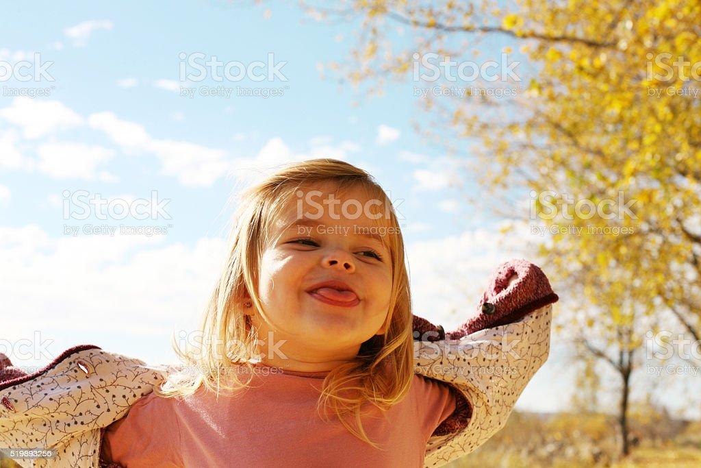 Cheerful little girl having fun outdoor. stock photo