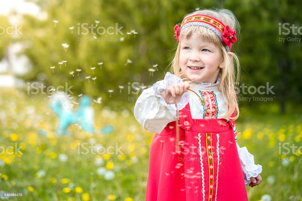 Cheerful  Little Girl Playing With Dandelion Fluff stock photo