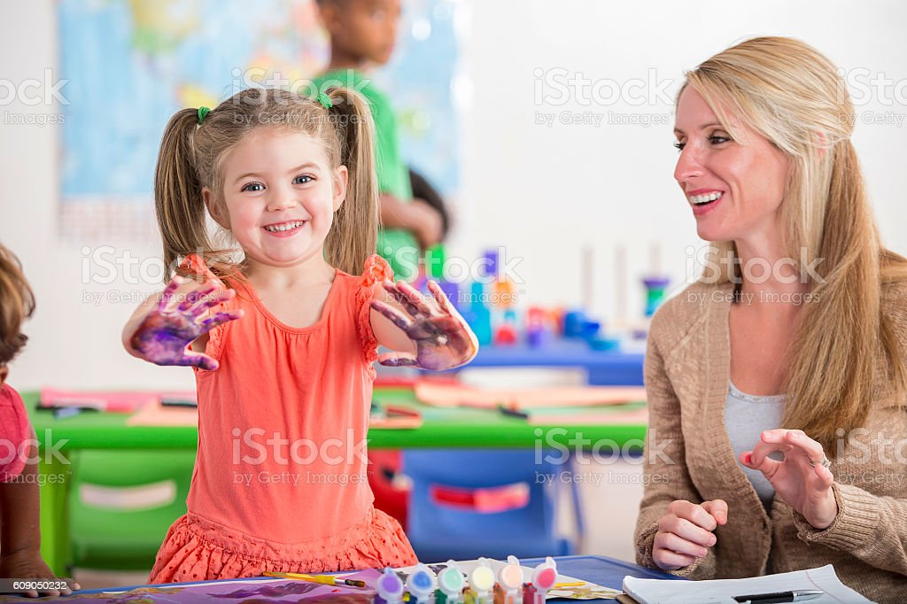Cheerful little girl shows off her painted hands stock photo