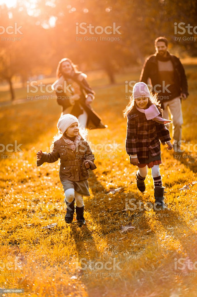 Cheerful little girls being chased by their parents in nature. stock photo