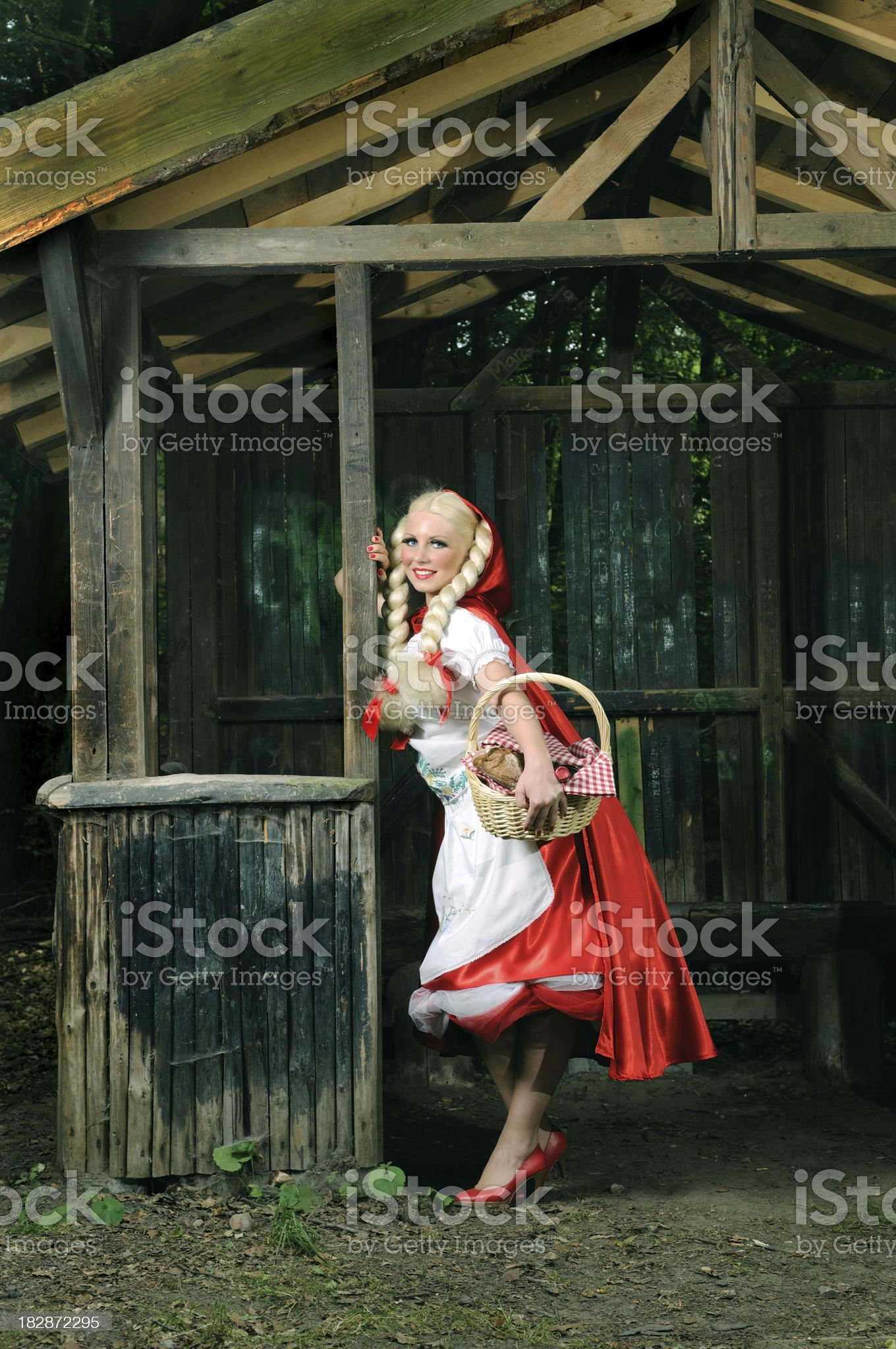 Cheerful Little Red Riding Hood Showing Her Basket royalty-free stock photo