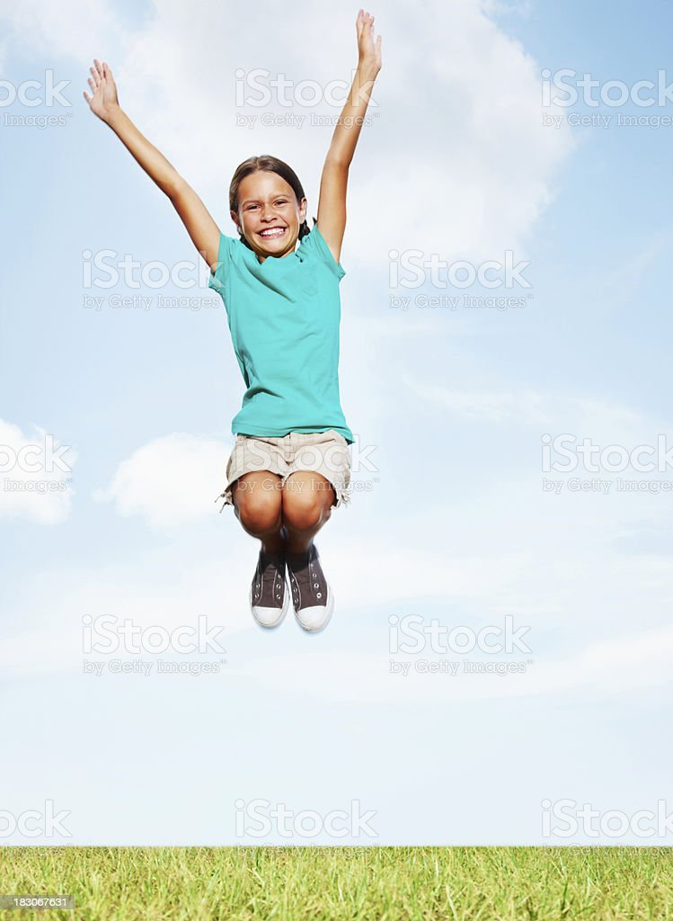 Cheerful littler girl jumping high in the air against sky royalty-free stock photo