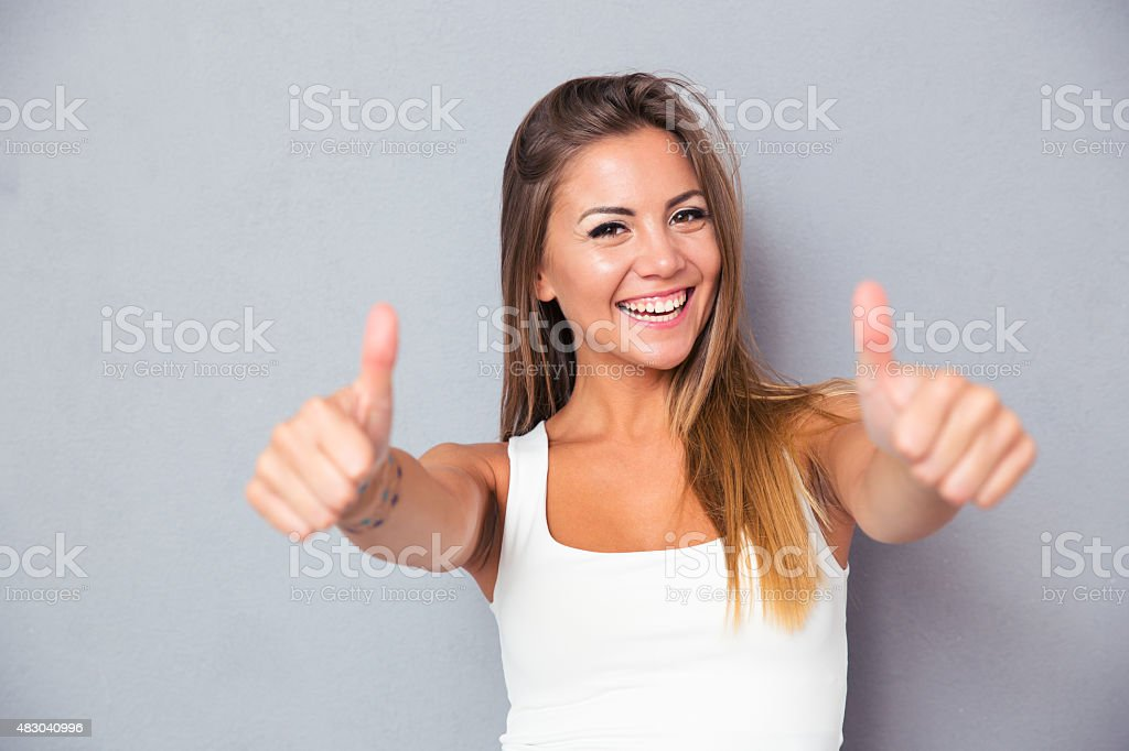 Cheerful lovely girl showing thumbs up stock photo