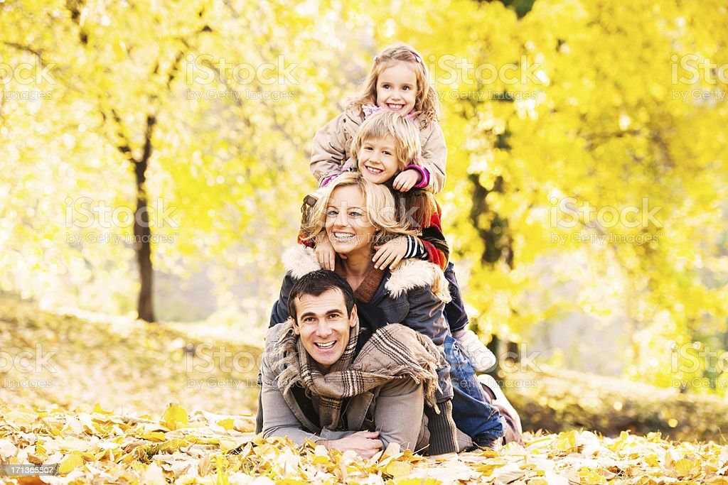 Cheerful loving family making human pyramid in park. royalty-free stock photo
