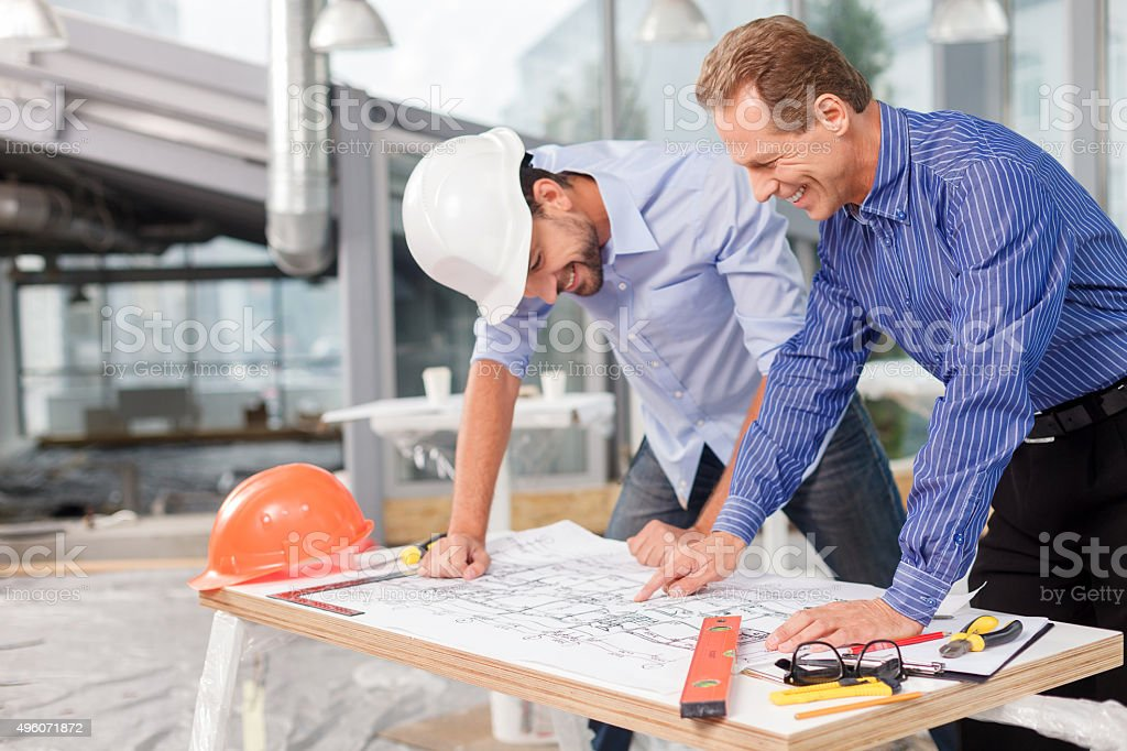 Cheerful male architects are discussing the project stock photo