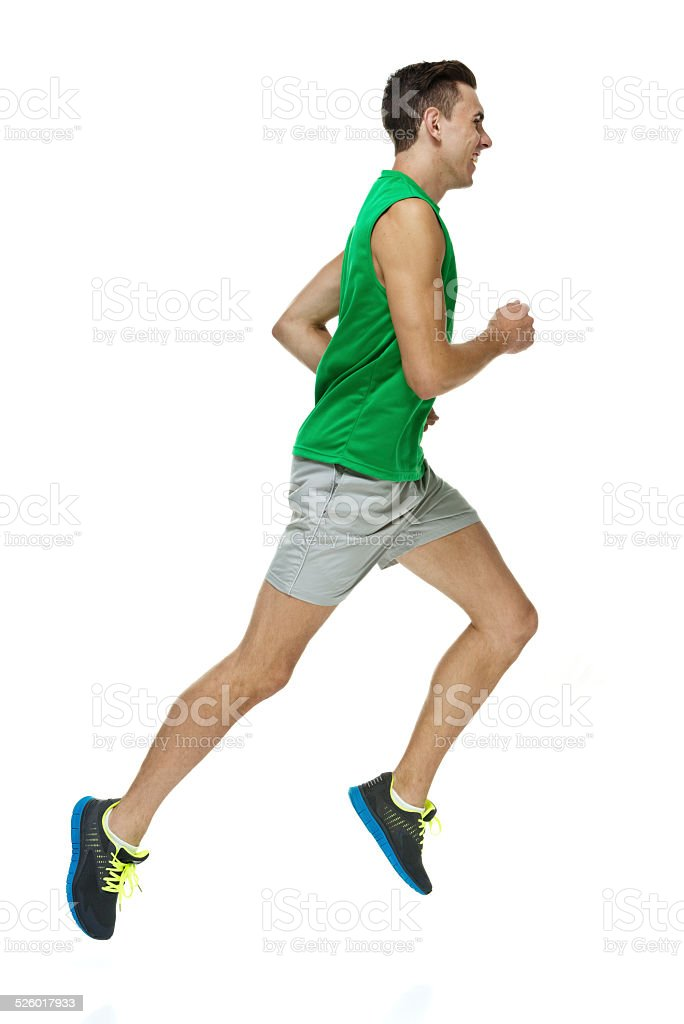 Cheerful male athlete running stock photo