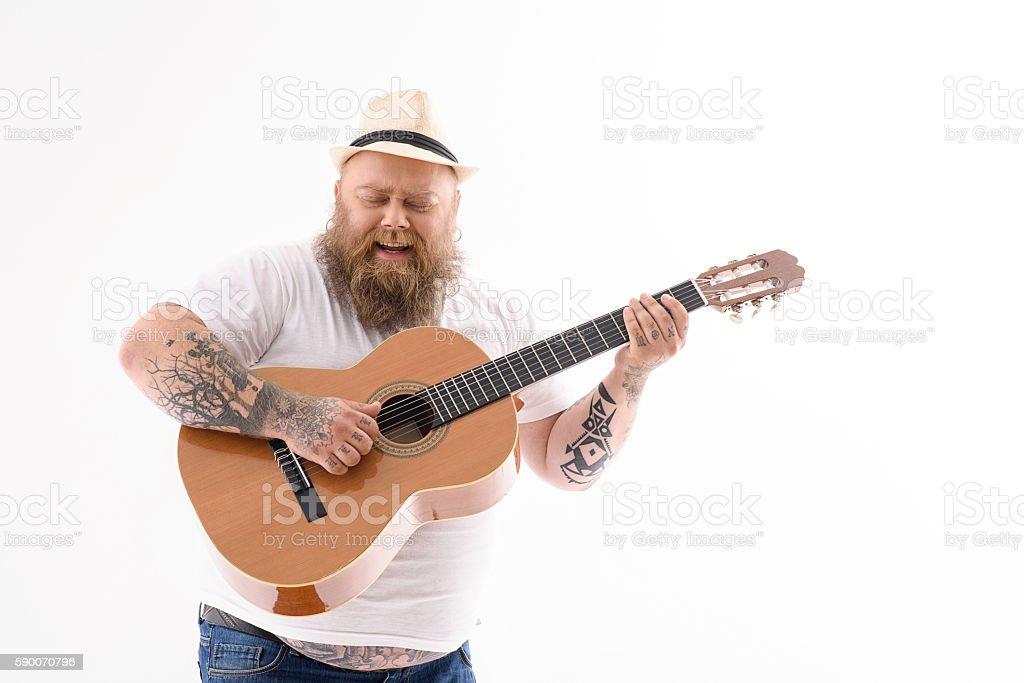 Cheerful male fatso playing guitar stock photo