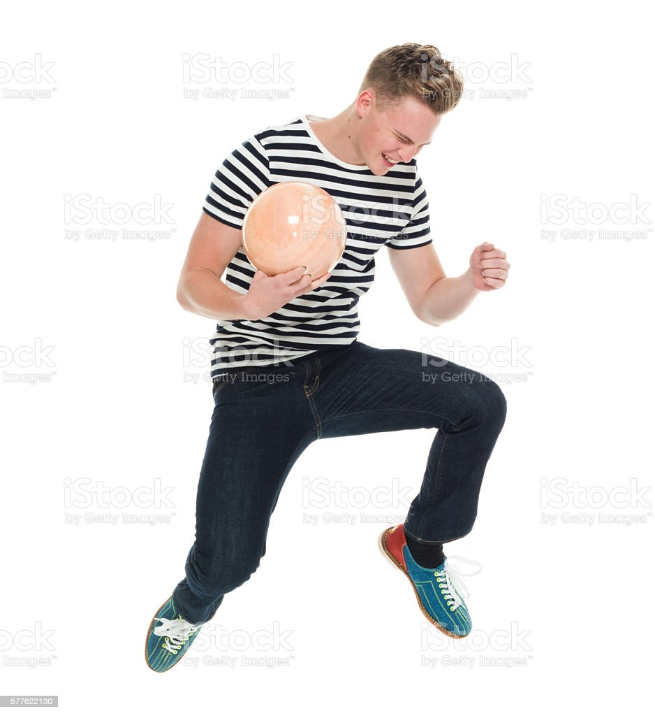 Cheerful male jumping with bowling ball stock photo