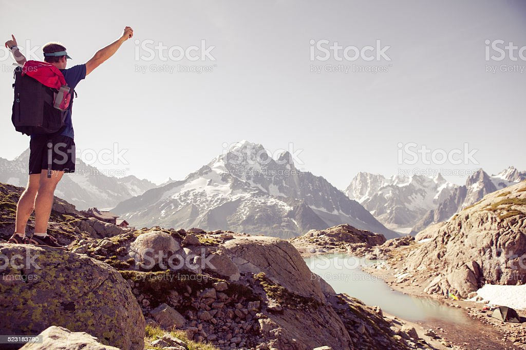 Cheerful male mountain top arms stretched out stock photo