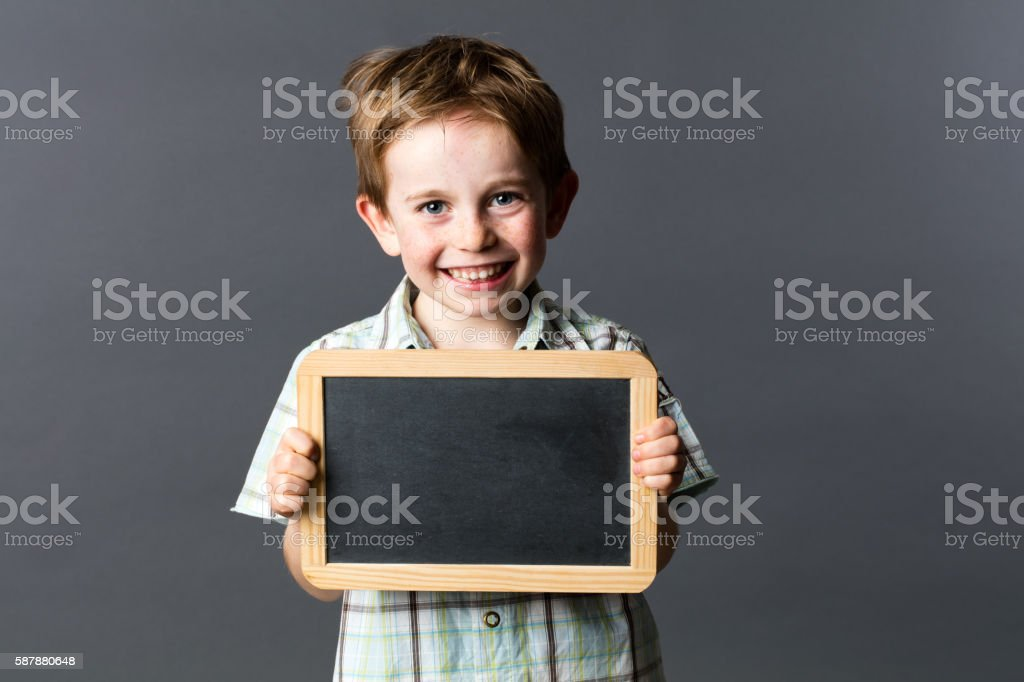 cheerful male preschooler proud to learn with writing slate stock photo