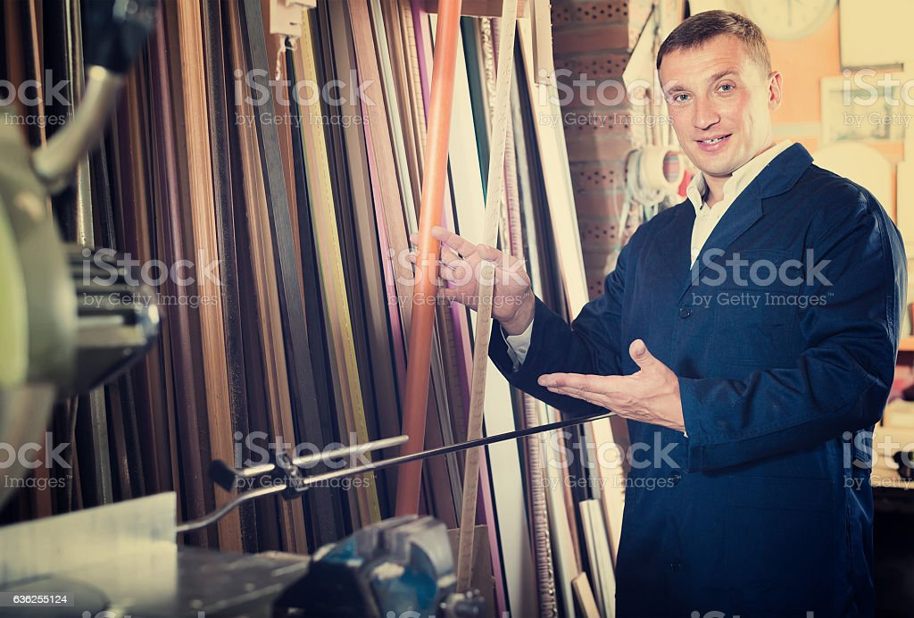 cheerful male seller in picture framing studio stock photo