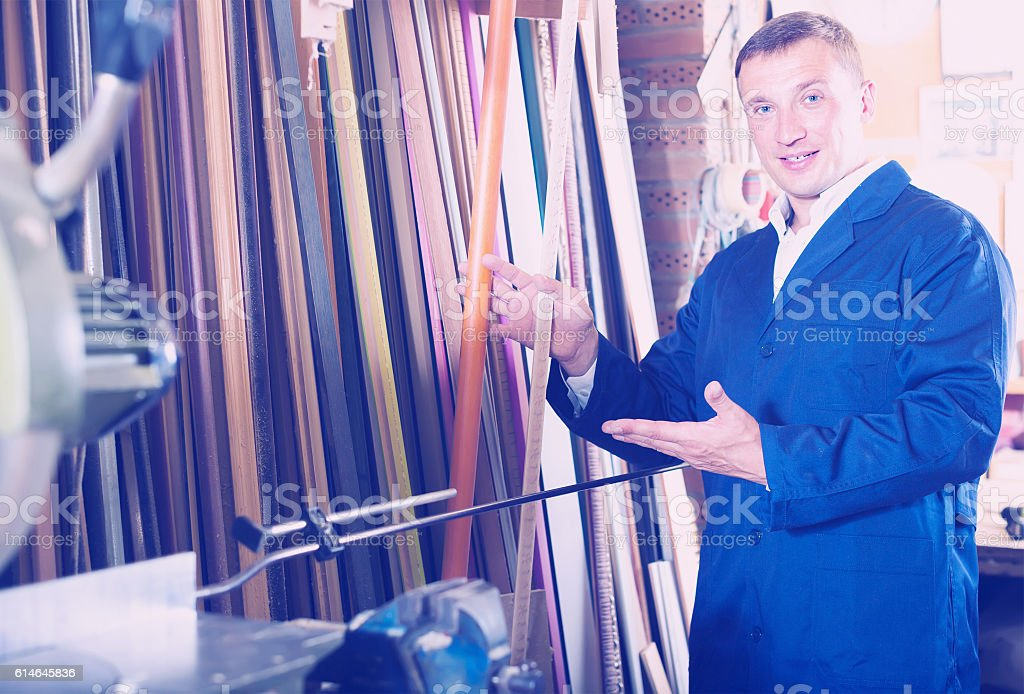 cheerful male seller in picture framing studio with wooden detai stock photo