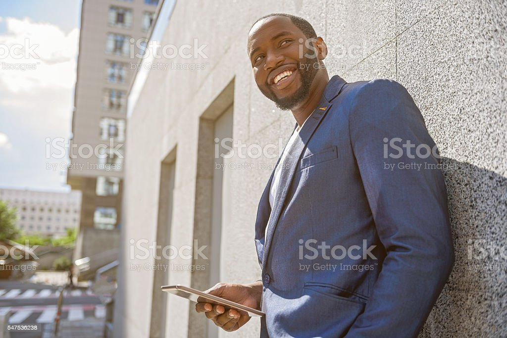 Cheerful male worker with modern technology in town stock photo