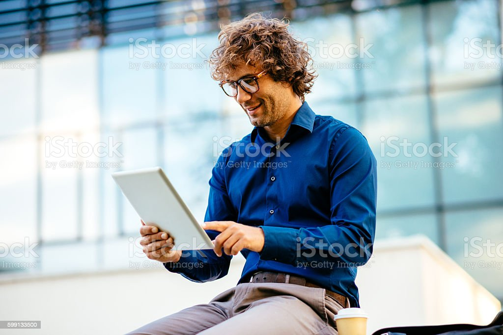 Cheerful man drinking coffee and using digital tablet stock photo